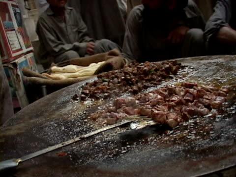 vídeos de stock, filmes e b-roll de september 15 2005 cu zo ms vendor cooking food for sale at stand people observing / peshawar pakistan / audio - espátula