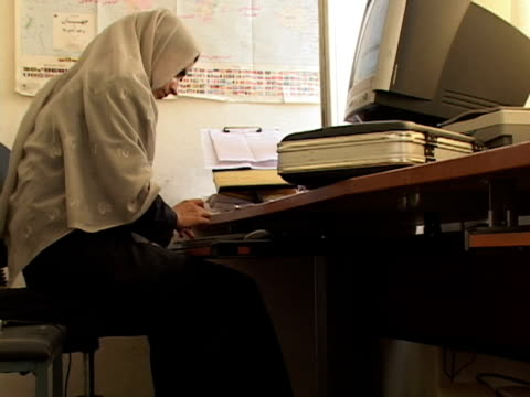 vidéos et rushes de september 15, 2005 woman in hijab using computer in office / kabul, afghanistan / audio - hijab