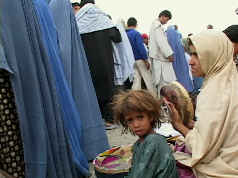 september 15 2005 ms woman with daughter in crowded street / kabul afghanistan / audio - kabul stock-videos und b-roll-filmmaterial
