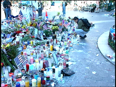 vídeos y material grabado en eventos de stock de september 16, 2001 mourner lighting candle as a memorial in union square park among other candles, flowers, and american flags / new york city, new... - 2001