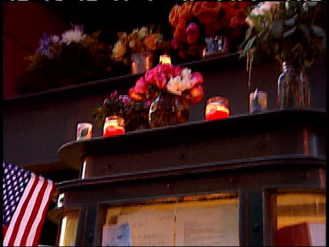 september 17, 2001 mourner looking at glass-covered memorial case containing notes and photographs surrounded by lit candles, flags, and flowers in... - back lit video stock e b–roll