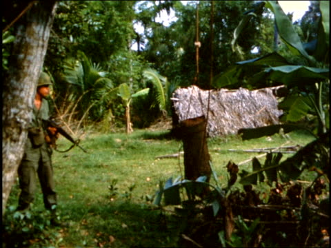 september 1967 ws a soldier intentionally sets off a booby trap in jungle / vietnam - ブービートラップ点の映像素材/bロール