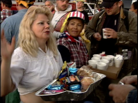 September 2001 2 female Salvation Army volunteers serve male volunteer workers food drinks Blonde says We'll be here as long as you guys are here