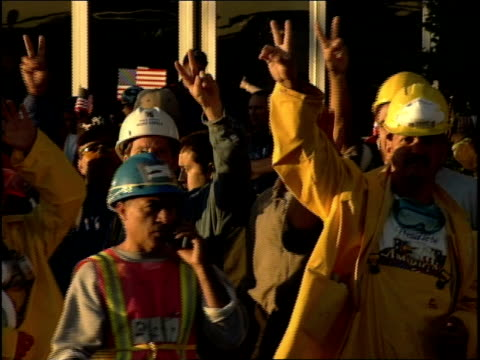 September 2001 Crowd of Ground Zero volunteers in hardhats at Jacob Javits center give peace / victory hand sign thumbs up wave