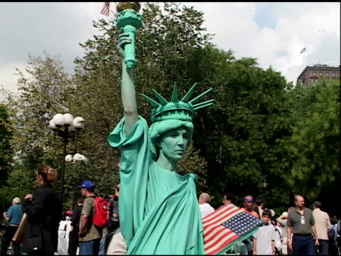 September 2001 Female performance artist dressed as Statue of Liberty standing perfectly still in Union Square African American female street vendor...