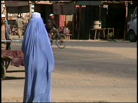 september 2002 afghanistan street scene w/women in burqas and men riding bicycles - 2002 stock videos & royalty-free footage
