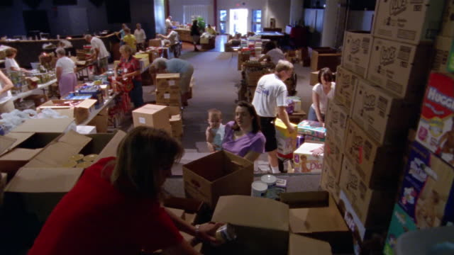september 2005 high angle wide shot woman holding baby talking to volunteer sorting cans of food at hurricane katrina relief center / volunteers... - donation box stock videos & royalty-free footage