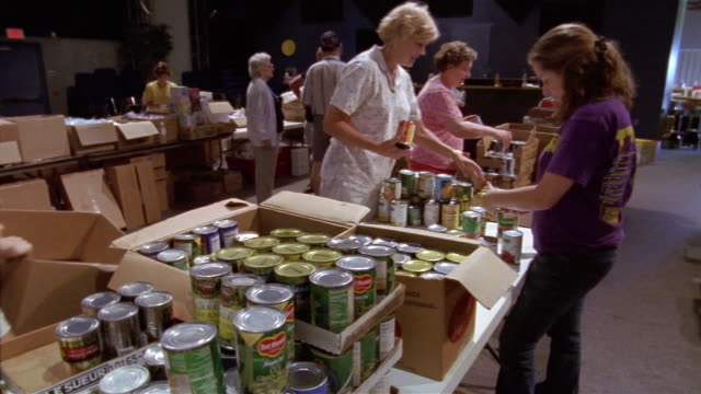september 2005 medium shot pan volunteers sorting canned goods and packing boxes at hurricane katrina relief center / woman holding up bag of potato... - tin stock videos & royalty-free footage