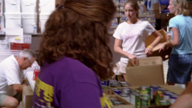 september 2005 medium shot pan volunteers sorting cans and packing boxes at hurricane katrina relief center / mississippi - tin stock videos & royalty-free footage