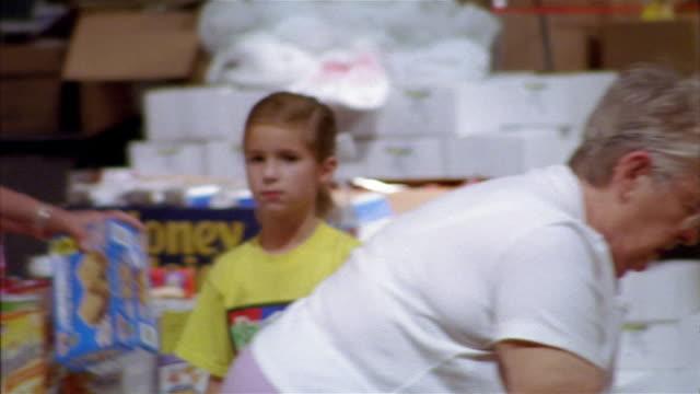september 2005 medium shot pan volunteers sorting food inside hurricane katrina relief center / mississippi - donation box stock videos & royalty-free footage
