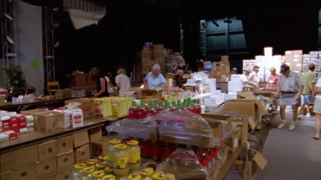 september 2005 wide shot pan volunteers sorting food and packing boxes inside hurricane katrina relief center / mississippi - donation box stock videos & royalty-free footage
