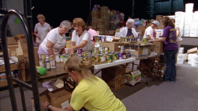 stockvideo's en b-roll-footage met september 2005 wide shot volunteers sorting cans and packing boxes at hurricane katrina relief center / mississippi - bukken