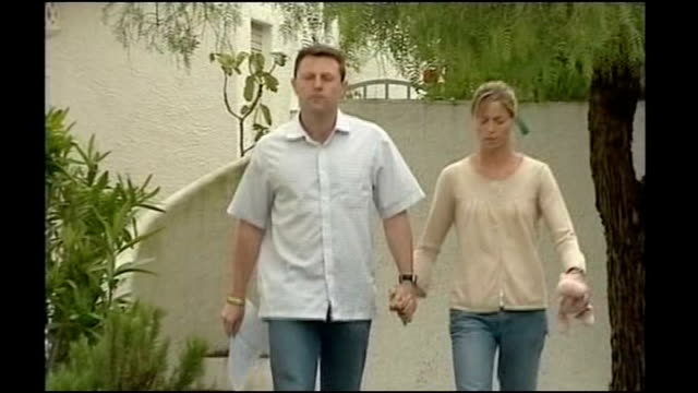 Praia de Luz Kate and Gerry McCann holding hands as along towards