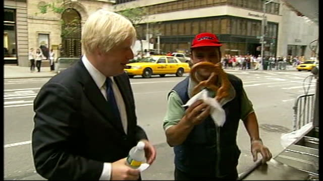 New York EXT Boris Johnson eating pretzel in street during visit Boris Johnson in Times Square
