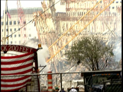 september 21, 2001 montage building's skeletal remains amidst smoldering rubble, flag draped fire truck, and pedestrians with face masks following... - rubble stock-videos und b-roll-filmmaterial