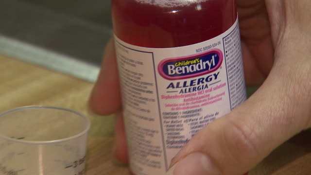 September 29 2010 ZO Consumer pouring liquid Children's Benadryl Allergy into measuring cup / United States