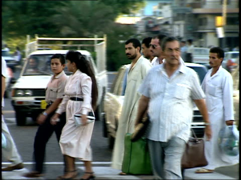 september 4 1990 ms pedestrians crossing the street on a busy afternoon / baghdad iraq - 1990 1999 stock-videos und b-roll-filmmaterial