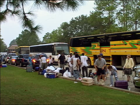 september 4 2005 wide shot evacuees gathering supplies at road side / tour buses lined up / hurricane katrina / new orleans louisiana - gabbietta per animali video stock e b–roll