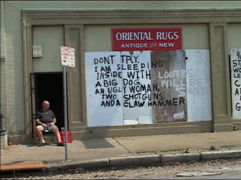 """vídeos de stock, filmes e b-roll de september 4, 2005 wide shot man sitting on step near spray-painted sign reading """"looters will be shot / don't try. i am sleeping inside with a big... - escrita ocidental"""