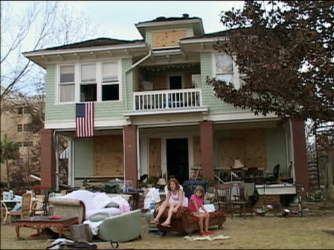 September 4 2005 Wide shot two little girls sitting on furniture strewn on lawn in front of house after Hurricane Katrina / New Orleans Louisiana