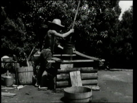 september 9, 1948 ws bare-chested man drawing water in bucket from well using long pole / tokyo, japan - 1948 stock-videos und b-roll-filmmaterial