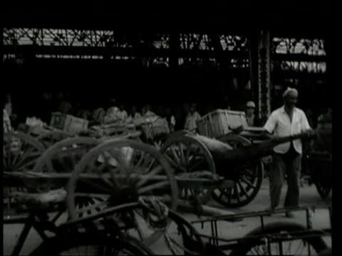september 9, 1948 ws men pulling carts with goods through warehouse / tokyo, japan - 1940~1949年点の映像素材/bロール