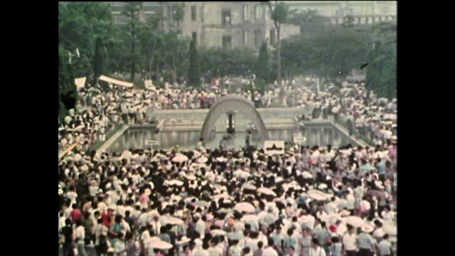 seq. large crowds of people in hiroshima peace park; 1975 - sad old asian man stock videos & royalty-free footage