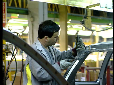 stockvideo's en b-roll-footage met seq men working on renault car production line tgv computers working on renault chassis lib england: birmingham: longbridge: ext gvs workers arriving... - chassis