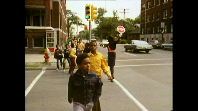 seq. of children crossing a road with guard; detroit, 1972 - detroit michigan stock videos & royalty-free footage
