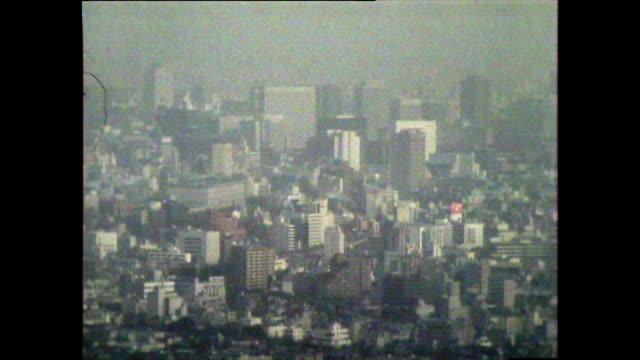 stockvideo's en b-roll-footage met seq. of has over tokyo cityscape covered in smog; 1981 - establishing shot