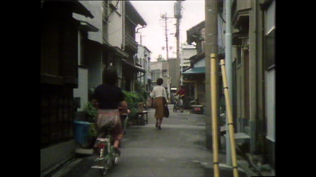 seq. of people cycling through tokyo side streets; 1981 - narrow stock videos & royalty-free footage