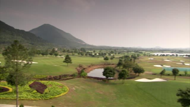 vídeos y material grabado en eventos de stock de sequence across a golf course near hanoi, vietnam. - golf cart