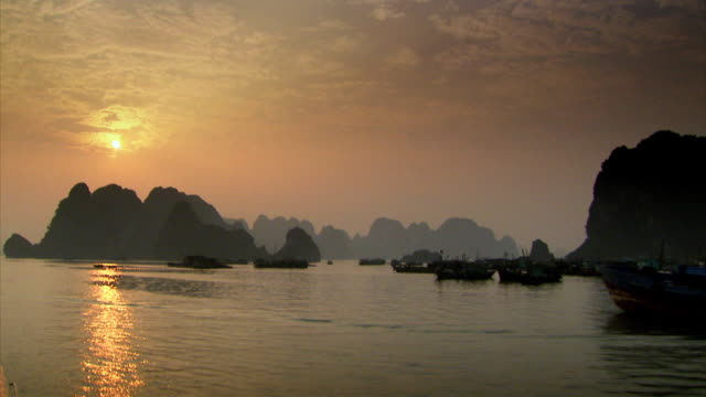 sequence across ha long bay at dusk. - halong bay stock videos and b-roll footage