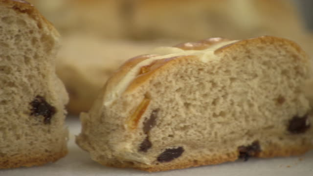stockvideo's en b-roll-footage met sequence demonstrating the difference between under-baked and properly-baked hot cross buns in a bakery, uk. - rozijn