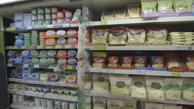 sequence including a handheld tracking shot of a dairy aisle at a large uk supermarket. - milchprodukte stock-videos und b-roll-filmmaterial