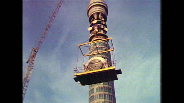 sequence installing satellite dishes on bt tower, london; 1983 - helmet stock videos & royalty-free footage