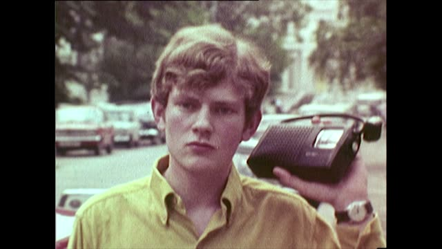 sequence of 1960s teenagers listening to portable radios - bbc archive stock-videos und b-roll-filmmaterial