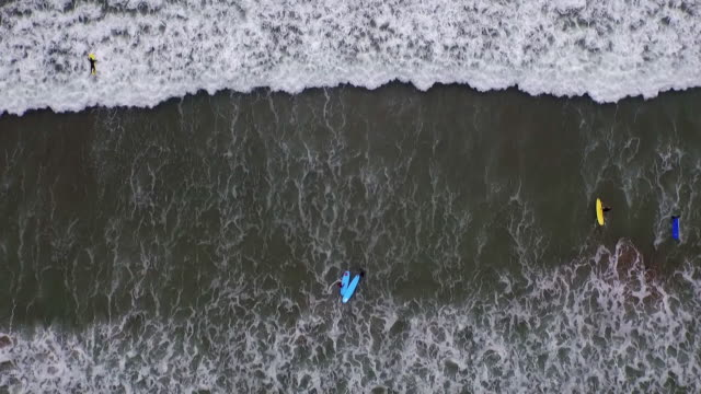 sequence of aerial shots showing a learner surfer and teacher in gentle waves in county clare in the republic of ireland. - ireland stock videos & royalty-free footage