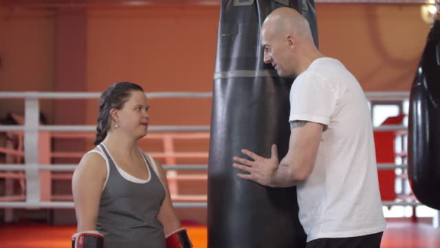 sequence of boxing coach talking with young woman with down syndrome - sequential series stock videos & royalty-free footage