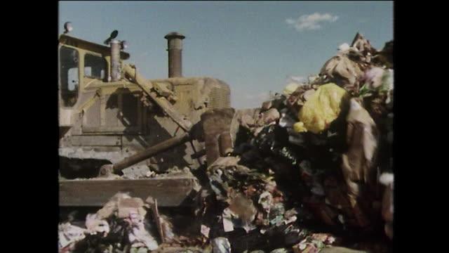 sequence of bulldozers moving rubbish on a landfill site; new york, 1975 - slit och släng bildbanksvideor och videomaterial från bakom kulisserna
