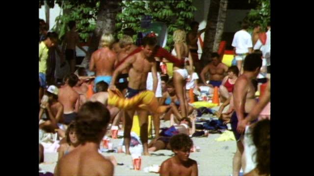sequence of crowds on waikiki beach in hawaii; 1985 - blickwinkel der aufnahme stock-videos und b-roll-filmmaterial