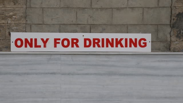 a sequence of drinking fountain tabs with a sign above them saying only for drinking - christian ender stock-videos und b-roll-filmmaterial