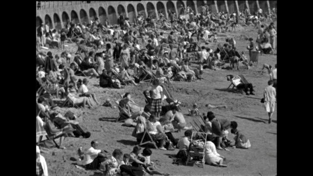 b&w sequence of families enjoying time at the seaside; 1963 - sunbathing stock videos & royalty-free footage