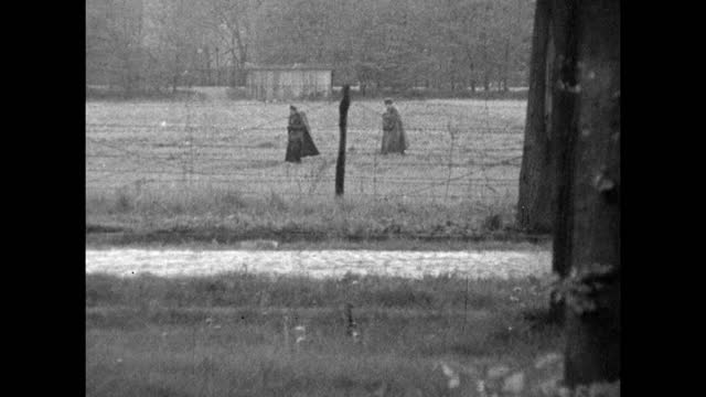 sequence of gvs of an unknown rural village on the east/west germany border; 1959. zoom out barbed wire fence around fields, pan over cobbled surface... - 1950 1959 stock videos & royalty-free footage