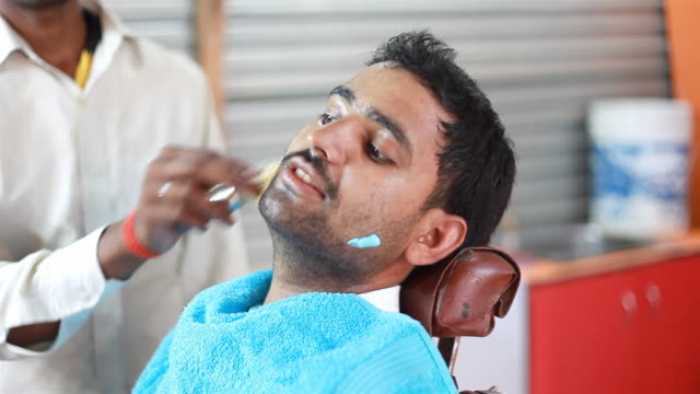 sequence of indian man getting shaving done in barber shop - towel stock videos & royalty-free footage
