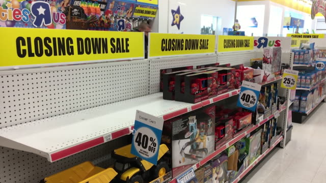 Sequence of internal shots showing 'closing down' signs and empty shelves in a Toys R Us store following their move into administration in London UK