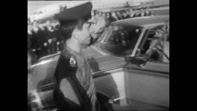 sequence of medium shots showing king hussein of jordan being followed to his car by press photographers after arriving at an airport in jordan; 1967. - mid adult stock videos & royalty-free footage