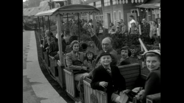 sequence of people enjoying train ride at battersea park fun fair; 1953 - moving past stock videos & royalty-free footage