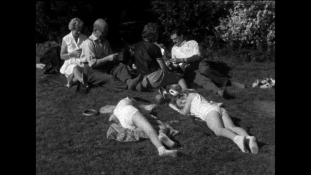sequence of people sunbathing in a park; uk, 1963. - 1963 stock videos & royalty-free footage