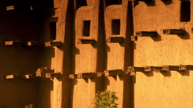vídeos de stock, filmes e b-roll de sequence of shots highlighting the exterior architectural features of the djinguereber mosque in timbuktu. - mesquita